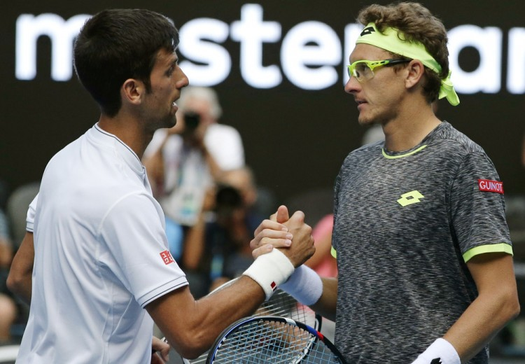 Novak Djokovic e Denis Istomin  se cumprimentam após o jogo (Mark Baker/Associated Press)